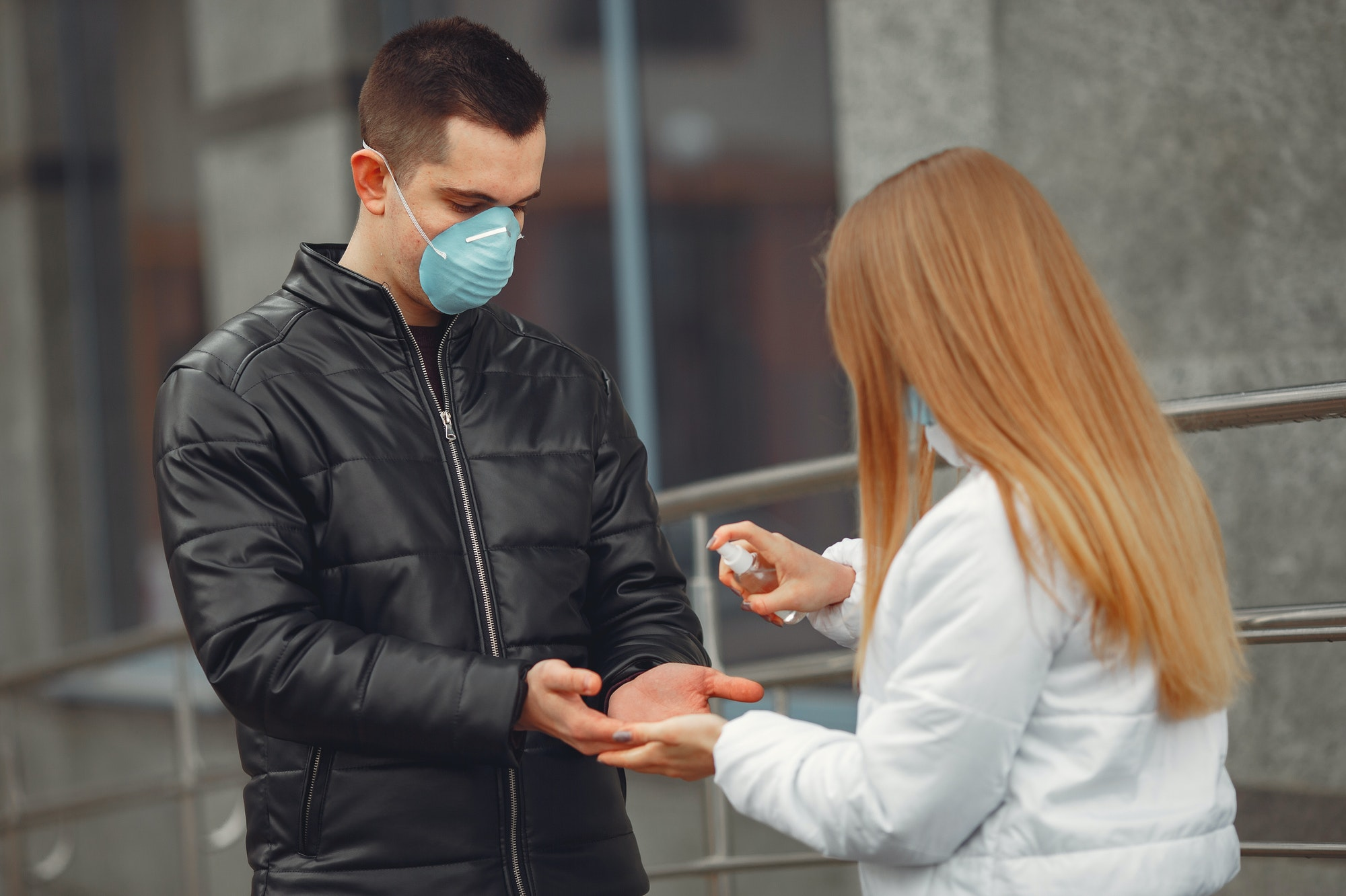 Young people wearing protective masks are spraying hand sanitizer