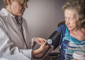 Doctor measures the arterial tension to oldster at home, Andalusia, Spain