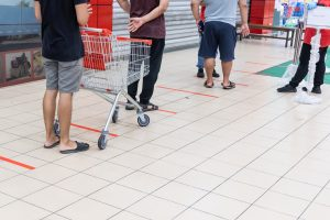 New normal lifestyle with social distancing in queue into supermarket.