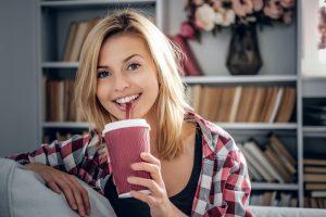 Blonde female drinks coffee.