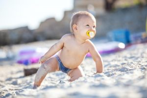 Cute baby boy playing on beach