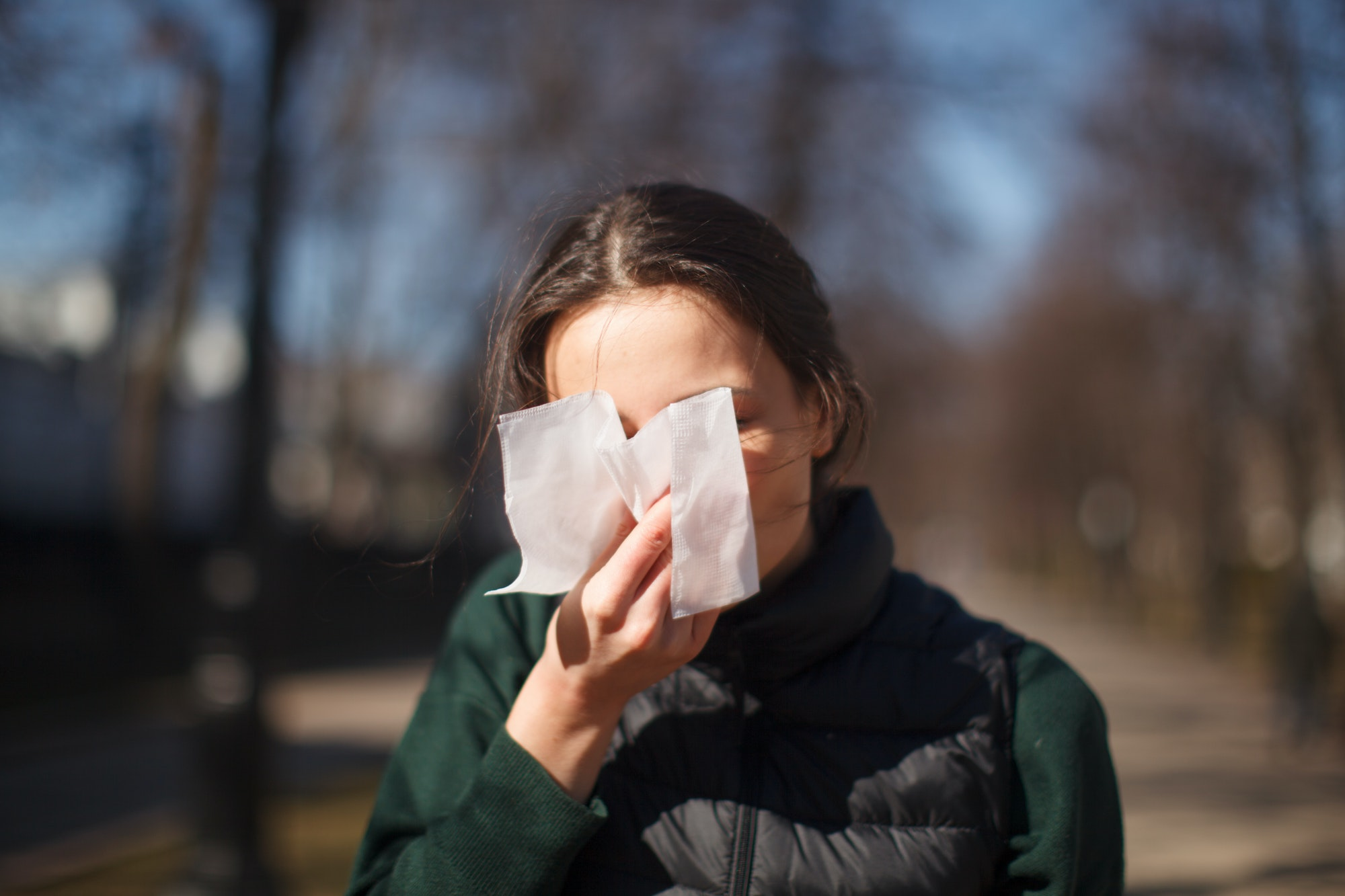 female outdoor sneeze and cover her face with napkin