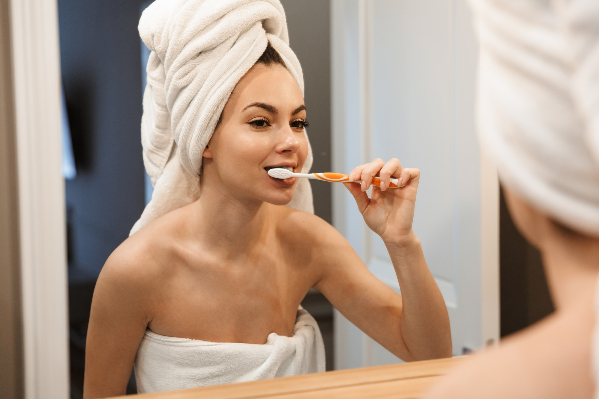 Image of smiling woman brushing teeth and looking at mirror