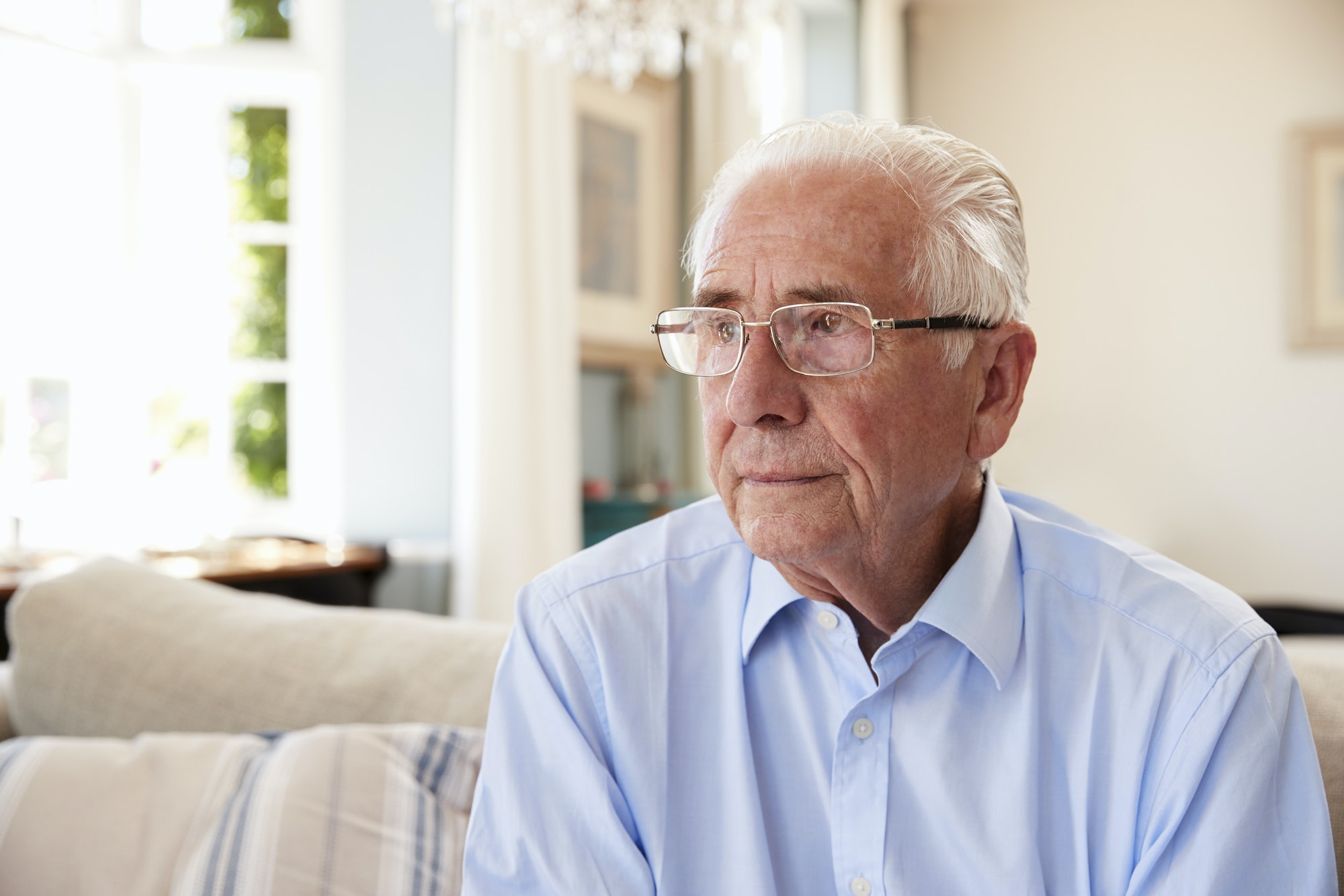 Senior Man Sitting On Sofa At Home Suffering From Depression