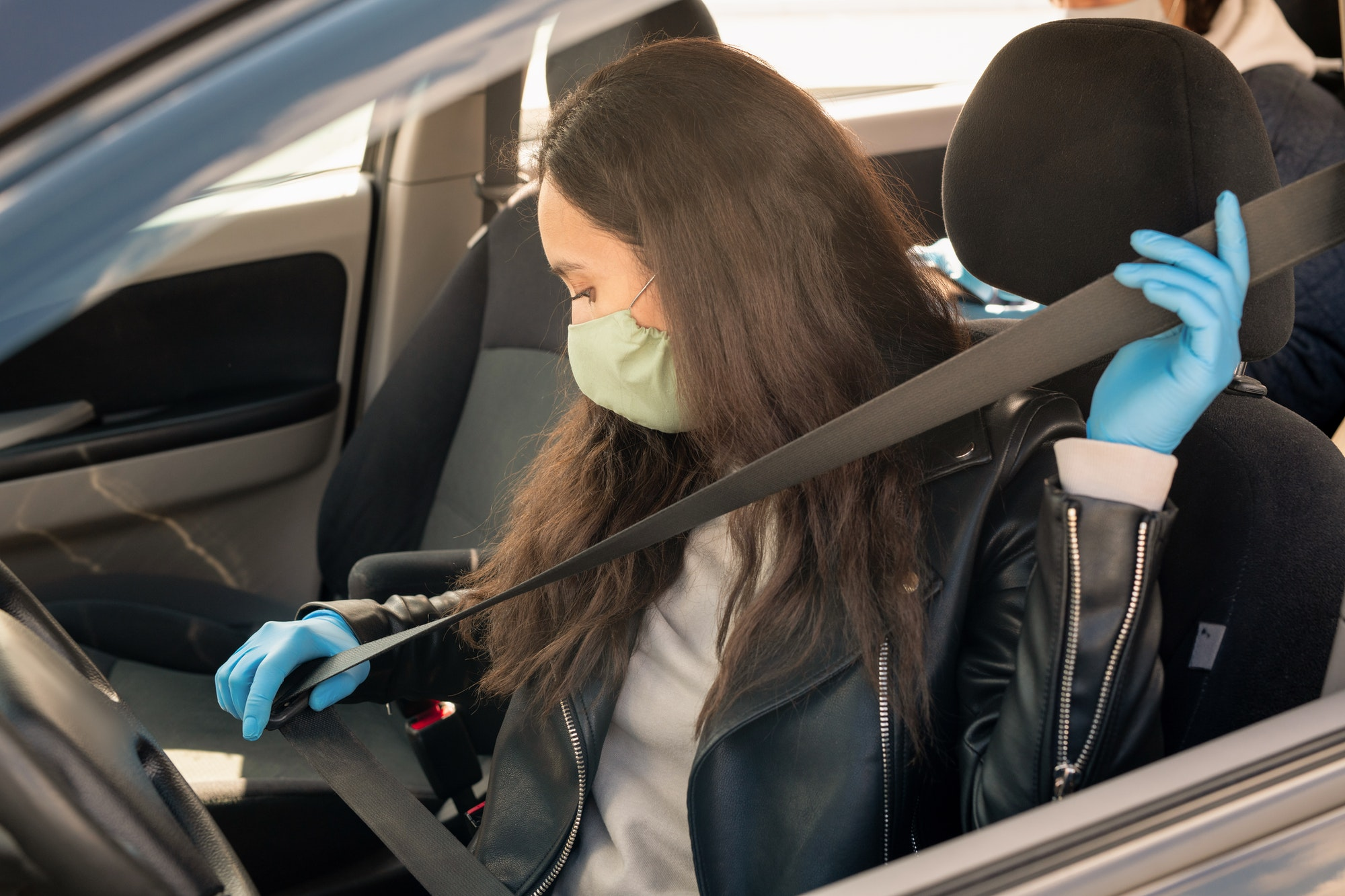 Young brunette female in leather jacket, gloves and mask fastening seatbelt