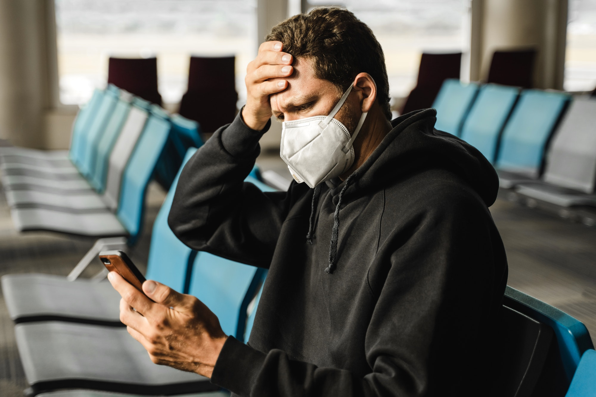 Men in respirator mask sitting at the airport, measuring temperature with palm and using mobile phon