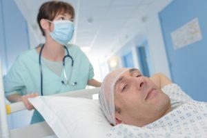 nurse taking patient on gurney into surgery