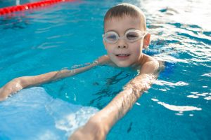 Positive little boy swimming with kickboard