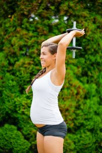 Pregnant Woman Performing Triceps Extension Exercise In Park