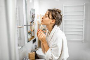 Woman looking on her skin at bathroom