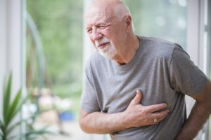 Senior grey man home alone having a heart attack