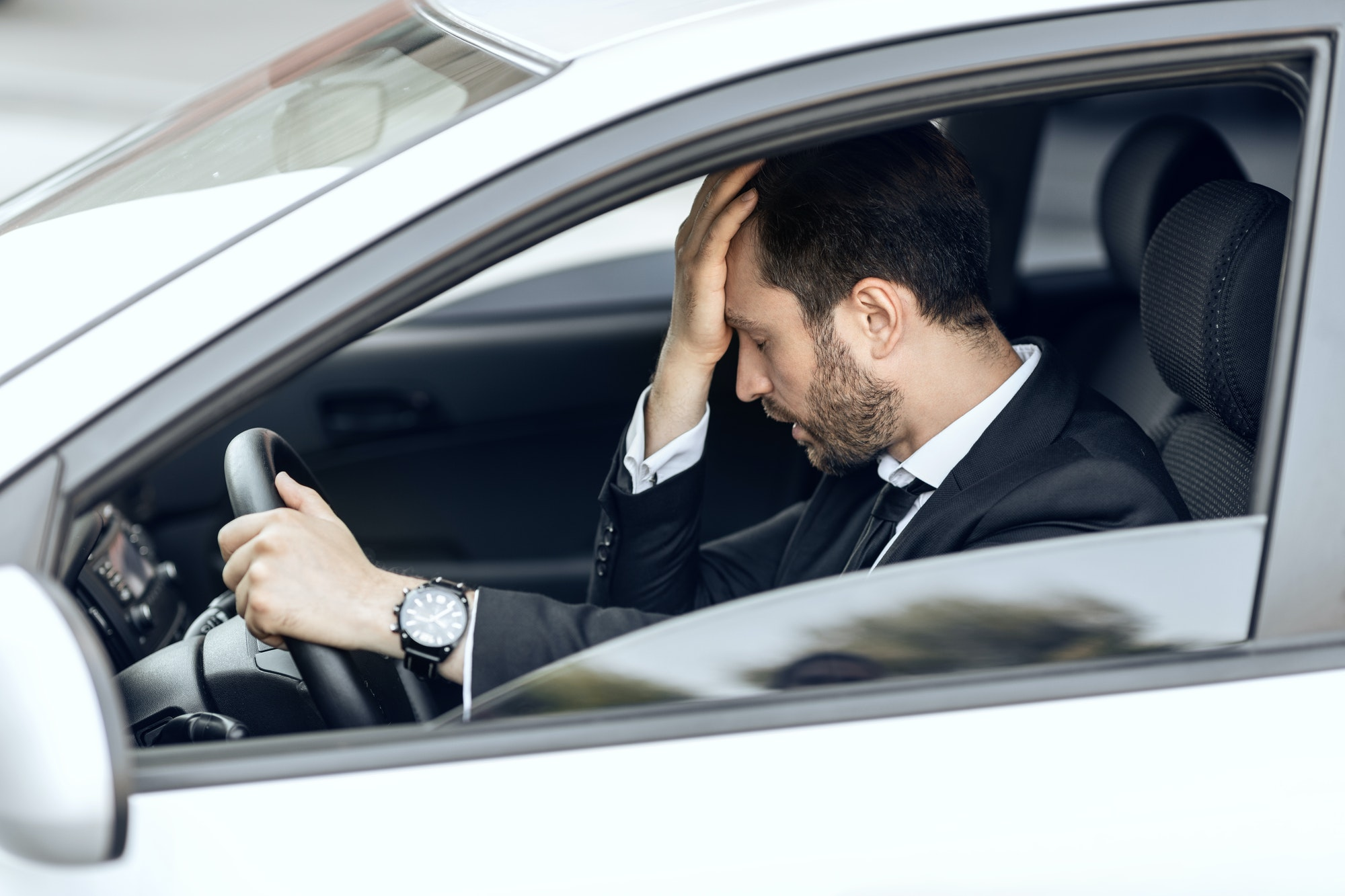 Stressed businessman stuck in traffic, late to airport
